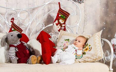 baby and new year, baby looks away lying on a sofa among pillows and toys on New Year's theme, next to the baby lies a gray mouse Archivio Fotografico - 133672480