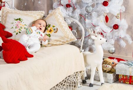baby and new year, baby with fingers of his right hand in his mouth lies on a sofa among pillows and toys on the background of a Christmas tree and gifts on a Christmas theme Archivio Fotografico - 133672484