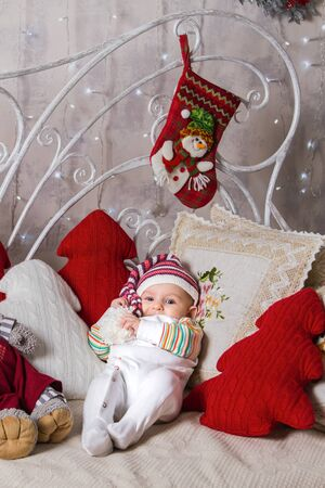 baby and new year, a baby in a knitted hat lies on a sofa among toys on a Christmas theme, smiles and holds in his hands the pompom of his hat Archivio Fotografico - 133672501
