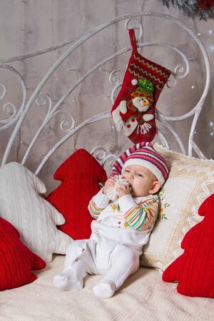 a baby in a knitted hat lies on a sofa among toys on a Christmas theme, holds in his hands and in his mouth the pompom of his hat Archivio Fotografico - 133672514