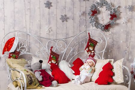 baby and christmas, a baby in a knitted hat lies on a sofa among toys on a Christmas theme, holds in his hands and in his mouth the pompom of his hat, next to the baby lies a gray mouse Archivio Fotografico - 133672512