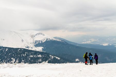 high in the mountains is a group of three people, in the background is Hoverla Mountain, Carpathians, Ukraine. Stock Photo