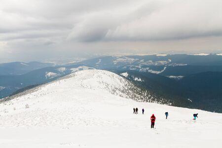 Eine Gruppe von Menschen erhebt sich auf einem Hochplateau auf den Gipfel des Berges. Im Hintergrund sind die Gipfel der Karpaten, Ukraine.