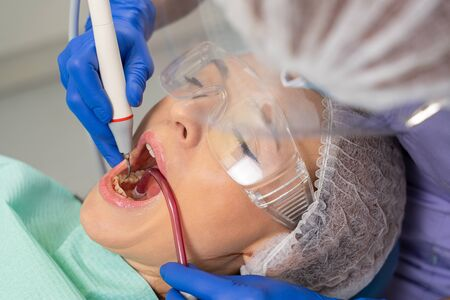 at the dentist's appointment. / Close-up of a girl's patient at the moment when the dentist is using her ultrasound and saliva pump to clean her teeth from tartar. Stockfoto