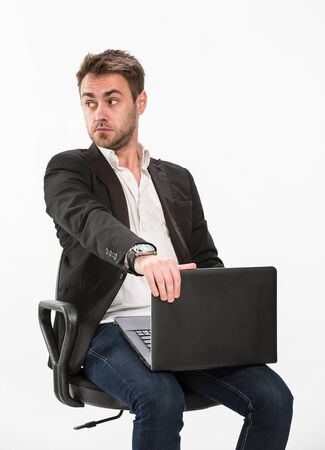 a tired clerk sits on an office chair and looks surprised to the right, holds a laptop in his hands, studio, white background.