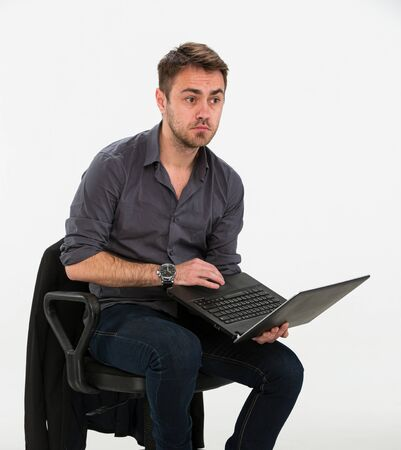 a tired clerk works with a laptop in his hands while sitting on a chair, looks in confusion in front, studio on a white background.