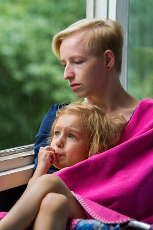 Mother and daughter are sitting by the open window during the rain, mother is holding her daughter in a blanket on herself, mother and daughter are sadly watching the rain through the window.