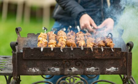 man cooks barbecue, in the process of cooking rotates a skewer with meat, close-up