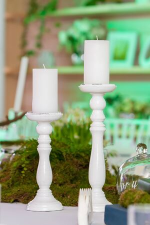 2 large white candles on white wooden cones stand on the table as part of table decoration, decor