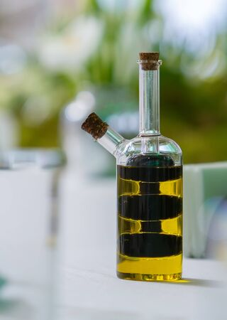 glass jar with oil in a vintage bottle stands on a served table