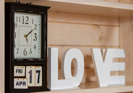 On the shelf are vintage watches that also indicate the date, month and day of the week: Friday April 17th. out of focus of the wooden letters is the word love . 스톡 콘텐츠