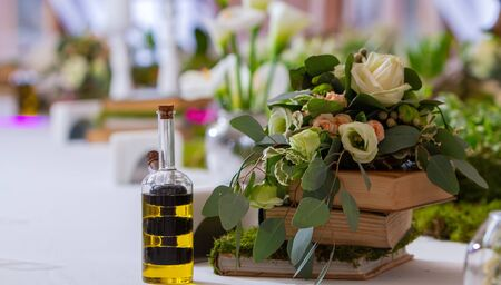 a glass vessel with oil in a vintage bottle stands on a served table next to the decor of books and flowers 스톡 콘텐츠