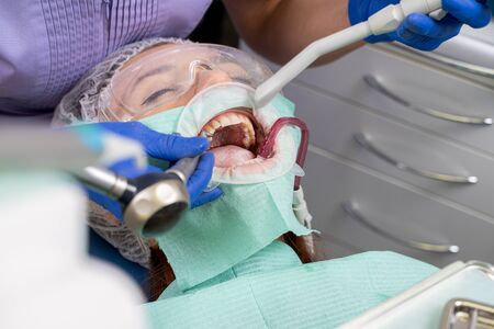 Close-up of the patient girl at the moment when the dentist is carrying out powder brushing with a special tool.