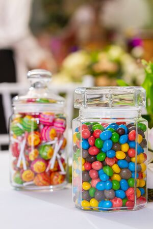 in the foreground is a glass jar with multi-colored sweets of oval-shaped dragee, in the background a glass jar with lollipops in a flowered wrap, out of focus. 스톡 콘텐츠