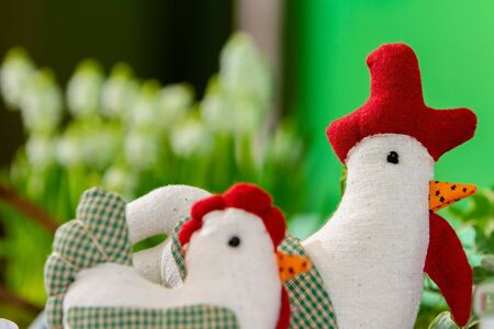 two sewn cloth dolls, in the form of a chicken and a rooster, stand on a served table in the form of table decoration. focus on the rooster doll, in the background. 스톡 콘텐츠