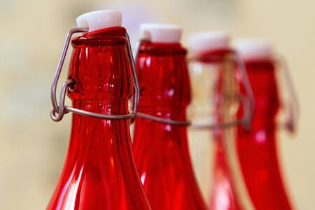 three glass bottles of red color and one transparent, with reusable corks on an iron bracket stand in a row, focus in the foreground on the first bottle of red color