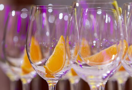 glasses with an orange slice set in several rows prepared for preparing drinks, close-up