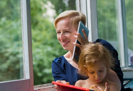 Mother and daughter by the open window, mother communicates cheerfully using a tablet, holds it near her ear like a telephone, daughter sits on her mother and examines her own hands.