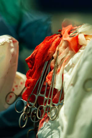 on bloody medical bandages, surgical clamps hang down to fix the thread for suturing the wound. close-up.