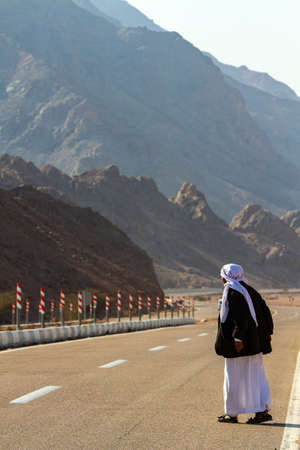 a Bedouin man stands on the road waiting for transport, Wady Megarah, Sinai, Egypt