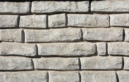 a fragment of a concrete figured wall of gray color in the form of a brickwork Stok Fotoğraf