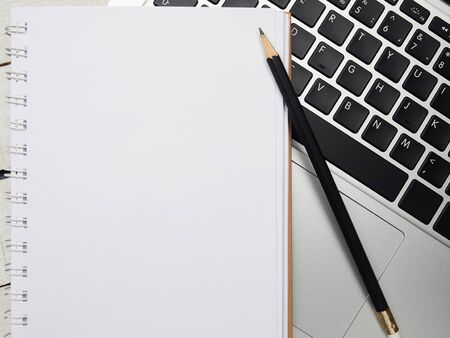 Workplace - laptop, notebook, pen, and pencil for remote work on a white wooden table. Freelance desktop for home or office. Background with copy space. Stock Photo