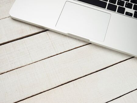 Workplace - laptop for remote work on a white wooden table. Freelance desktop for home or office. Background with copy space. Stock Photo