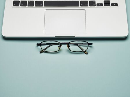 Workplace - laptop and glasses for remote work on a blue background table. Freelance desktop for home or office. Background with copy space. Banque d'images