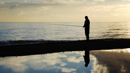 Fisher man with fishing rod silhouette on the beach at sunset photo