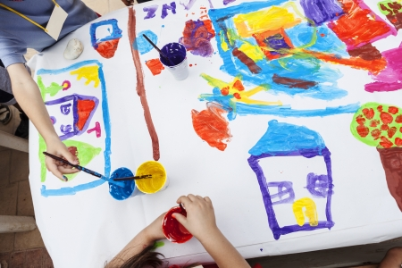 children painting with paintbrush and colorful paints photo