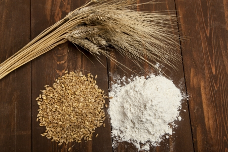 Wheat, plant seeds and flour on wooden table