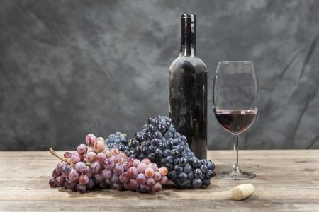 Rode wijn en druiven op een houten tafel Stockfoto