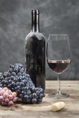 corcho: El vino tinto y uvas en una mesa de madera