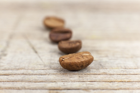 Brown coffee beans on wooden background, close up