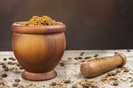 Mortar and pestle with brown coffee and coffee beans.