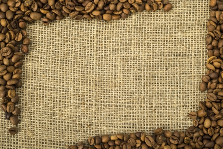 Frame of brown coffee beans on burlap. Stock Photo