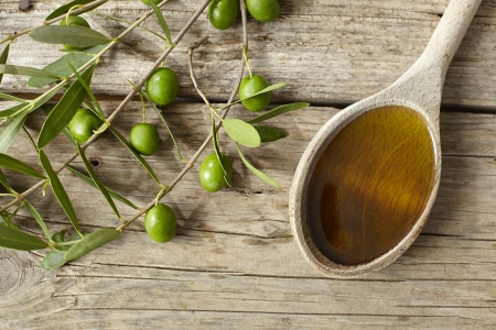 Green olive branch and a spoon full of oil on the wooden table