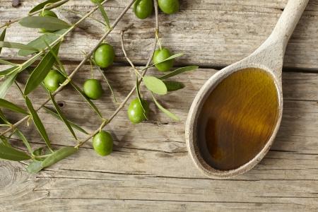Groene olijftak en een lepel vol met olie op de houten tafel