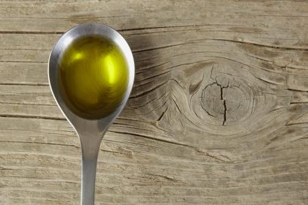 lepel vol met olijfolie op een houten tafel Stockfoto