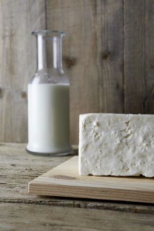 Fresh feta cheese with bottle of milk on a wooden table Imagens