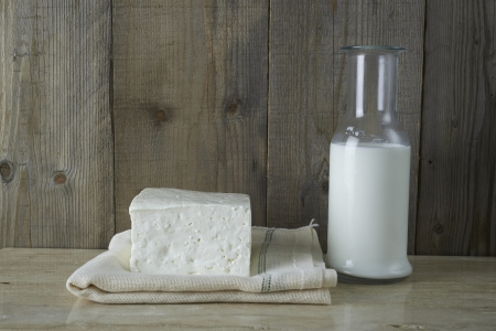 cubed: Fresh feta cheese with bottle of milk on a wooden table Stock Photo