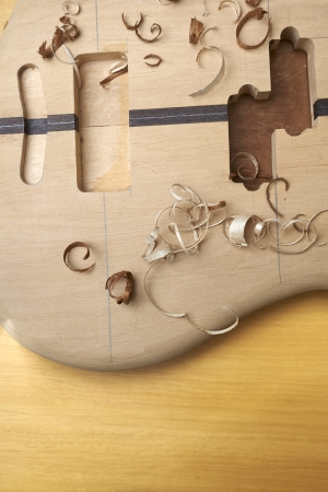 boehm: Bass guitar under construction, with tools and accessories. Stock Photo