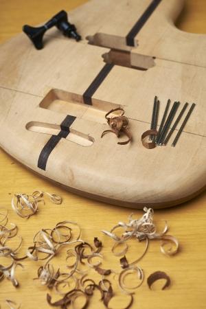 boehm flute: Guitarra baja en construcci�n, con herramientas y accesorios.