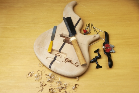 boehm flute: Bass guitar under construction, with tools and accessories. Stock Photo