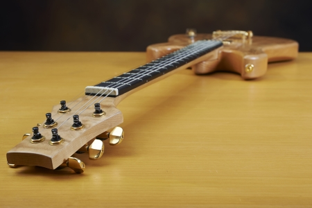 Guitar, wooden natural color with golden accessories. Stock Photo
