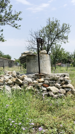 water well made of stones in countryside. photo