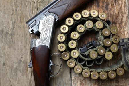木製の背景のカートリッジとビンテージ狩猟銃 写真素材
