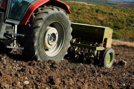seed drill: agricultural tractor sowing seeds and cultivating field