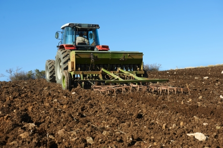 agricultural tractor sowing seeds and cultivating field photo