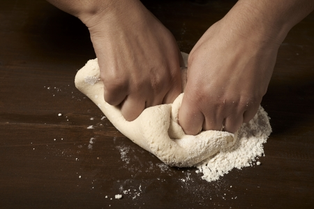 womans hands kneading dough on wooden table Stock Photo